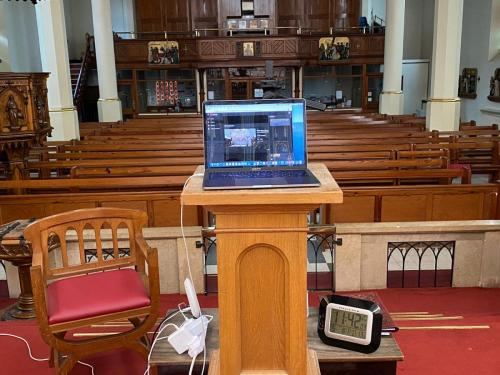 Cables ensure that the internet connection from the house is relayed into the church. The laptop is ready for YouTube live streaming.